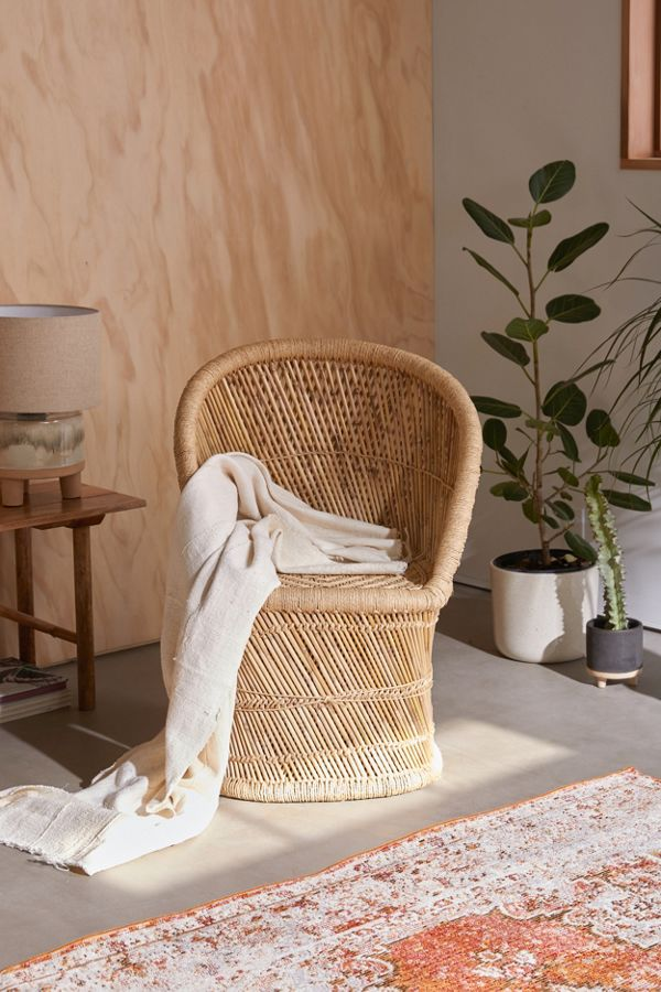 woven wicker chair by Urban Outfitters white throw blanket vintage style area rug potted greenery wood grain wall
