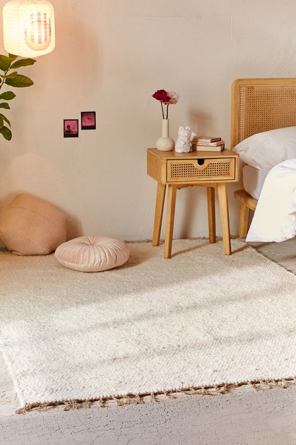 woven wool area rug in ivory light wood bedside table in midcentury modern style some floor pillows