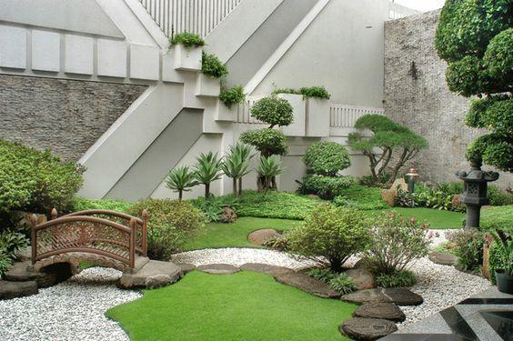 Japanese style backyard idea mini wooden bridge some grass beds natural stone walkway