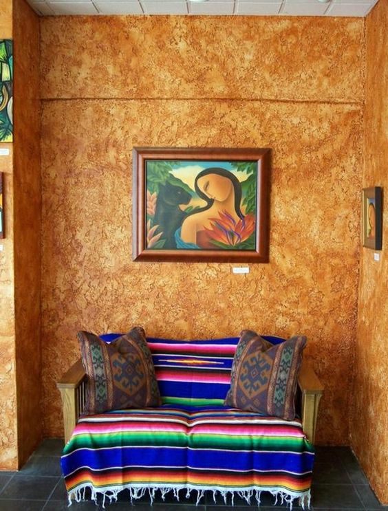 Mexican seating area more textural walls in earthy brown colorful striped loveseat with throw pillows