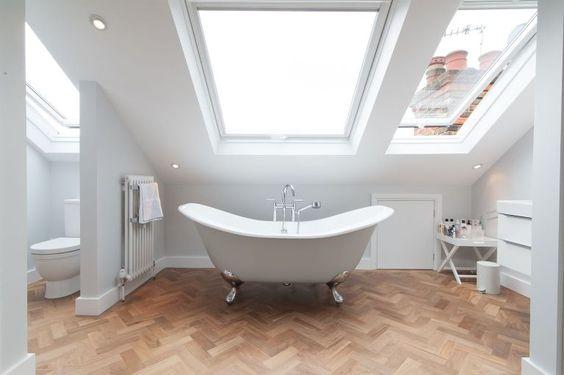 attic bathroom design with large skylights silver claw foot bathtub in white herringbone tiled wood floors