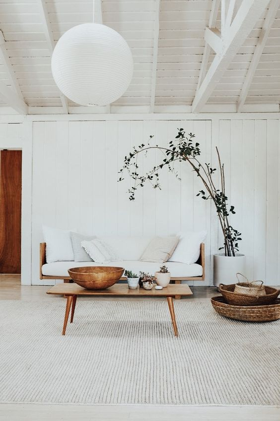 bright and airy living room midcentury modern sofa and table white planter with huge houseplant ornate baskets large area rug in white exposed wood plank ceilings oversized pendant lantern