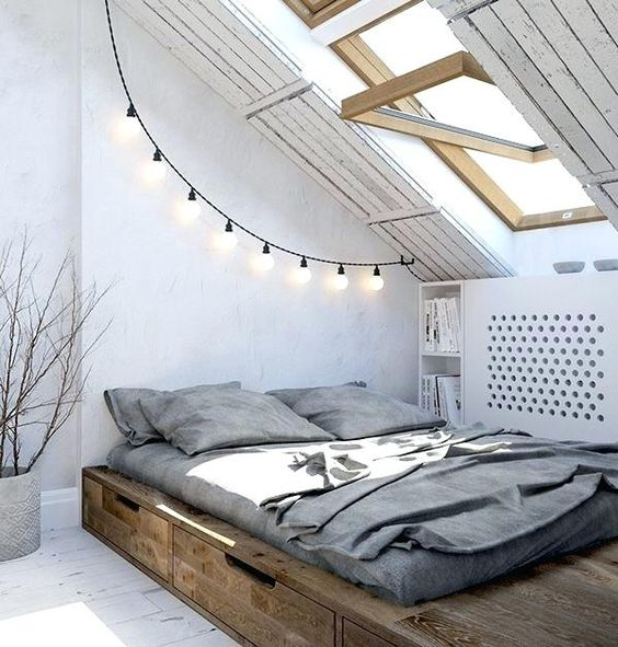 comfy bedroom in attic platform bed frame with under storage solution gray bed linen and shams slanted ceiling with wood framed skylight
