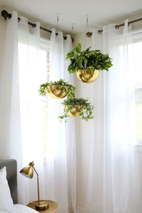 corner hanging indoor garden idea with hanging brass planters and vines white curtains