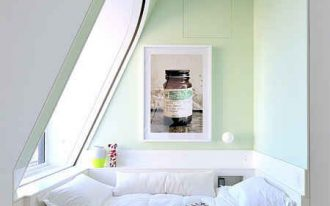 corner relaxing spot with slanted glass window daybed with white covered cushion and pillows small side table