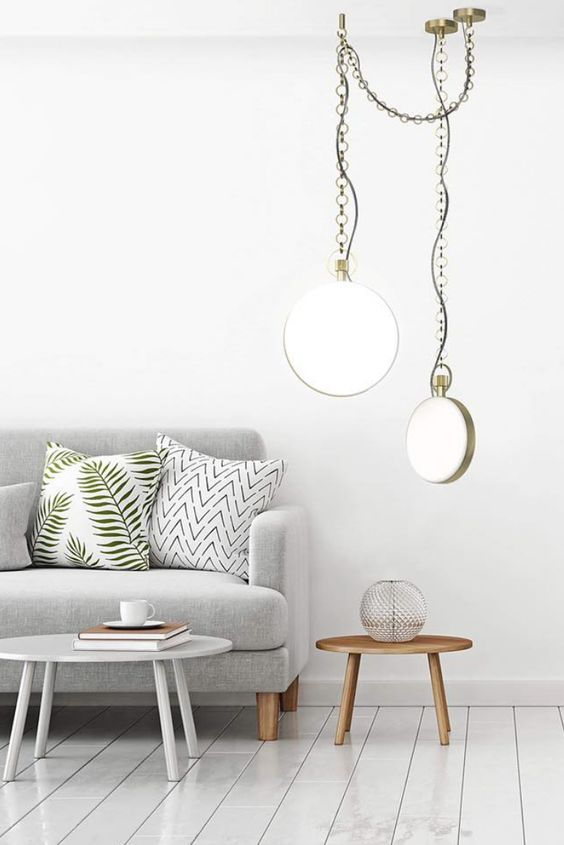 curved opaline glass lighting fixture with metal details on chains light gray sofa with throw pillows low profile side table with round top and made of wood