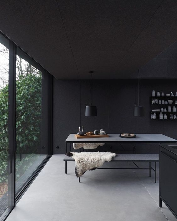 dark yet airy dining space black dining table black bench seats a couple of black pendants