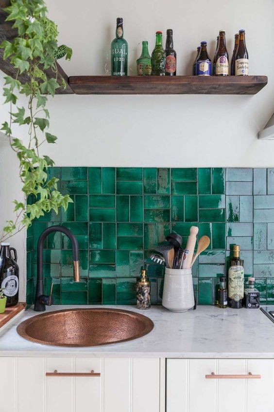 gloss green emerald tile backsplash copper sink white ceramic kitchen countertop white kitchen cabinetry dark wood display for greenery and ornate bottles
