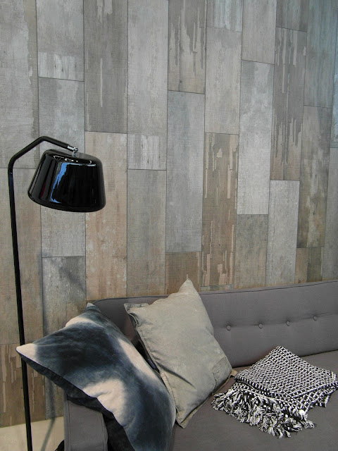 gray wood plank walls with natural stains gray sofa with throw pillows gloss black floor lamp
