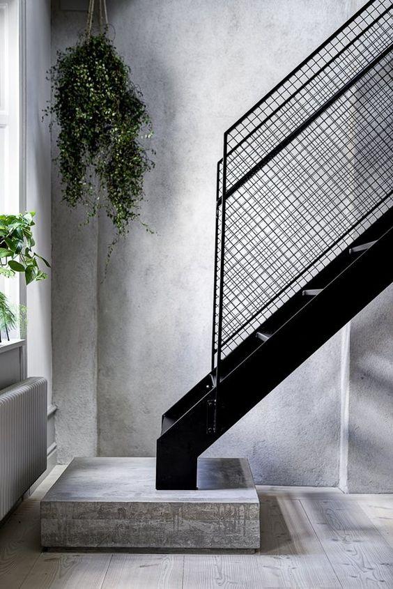 hard and heavy metal staircase with industrial details concrete walls and walls hanging greenery