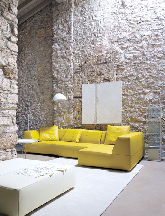 hard textured stoned walls modern minimalist sofa in yellow white area rug