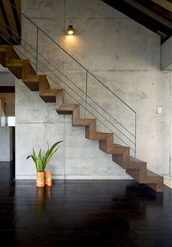 hardwood staircase with wired railing system industrial style spotlight fixture gloss black wood floors bare concrete walls