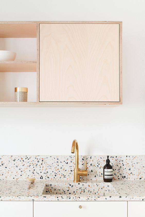 kitchen cabinetry in pastel multicolored backsplash and sink brass faucet