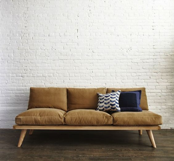 midcentury modern sofa with wood frame and gold toned cushions and also some throw pillows