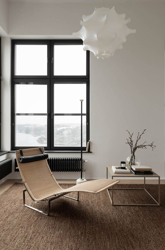 minimalist and inviting seating area simple lounge chair minimalist side table natural brown area rug crisp white wall black framed glass window