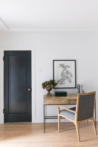 minimalist monochrome home office wood working desk with thin metal legs wood working chair with gray cushions light wood floors black painted door crisp white walls