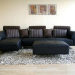 Opulant Black Leather Sofa With Striped Throw Pillows Leather Coffee Table In Black Textured Area Rug In Gray Light Wood Floors