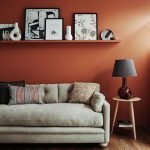 Rust Colored Wall Paint Floating Shelf For Monochromatic Displays Pale Toned Sofa With Throw Pillows Light Wood Side Table In Midcentury Modern Style