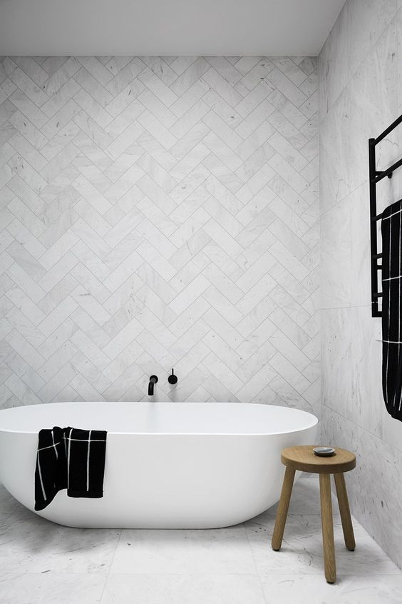 rustic minimalist bathroom white bathtub wood stool as the side table herringbone tile wall in white white floors
