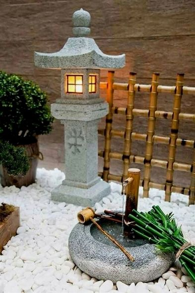small Japanese garden idea concrete outdoor Asian light fixture bamboo railing system mini bamboo fountain with concrete bowl white stone garden base