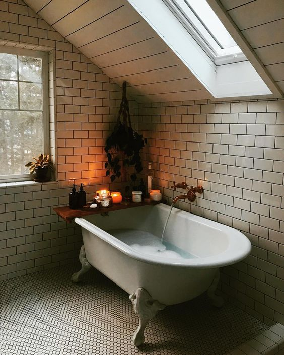 smaller attic bathroom design claw foot bathtub ceramic subway tile walls small hexagon tile floors slanted ceiling with skylight glass window with white wood trims
