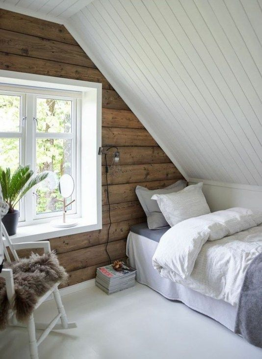 smaller bedroom in attic room single bed frame a rocking chair in white wood plank walls wood plank slanted ceilings glass window with white wood trims