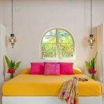 Warm White Stucco Like Walls Higher Ceilings Made Of Terra Cotta Curved Top Window With Trim A Couple Of Pendants Bright Yellow Bed Linen Vivid Pink Shams