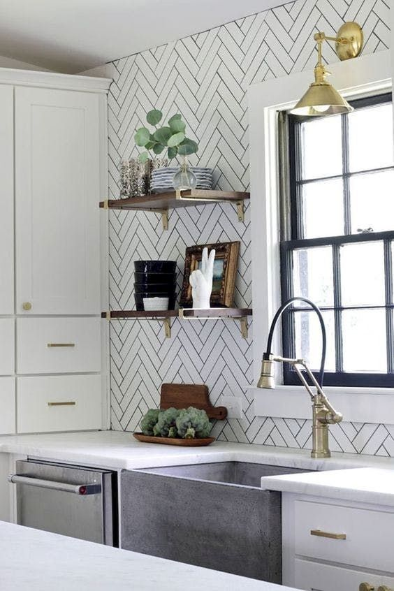 white herringbone tile backsplash with black grout farmhouse sink brass lamp over the sink white cabinetry wooden display racks