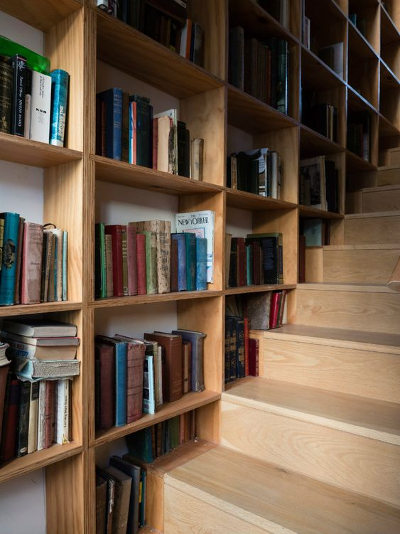 wood staircase with huge sized book shelving as its 'raililing system'