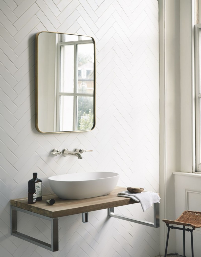 Scandinavian bathroom design with floating light wood sink with metal base brass framed wall mirror white herringbone metro tiled walls