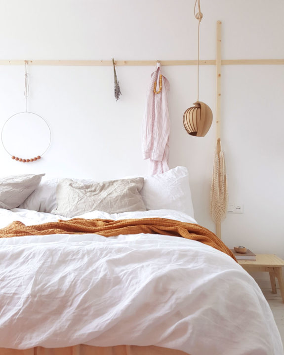 airy and bright bedroom idea pure white bed treatment rust throw blanket decorative light wood wall lining for hanging stuffs
