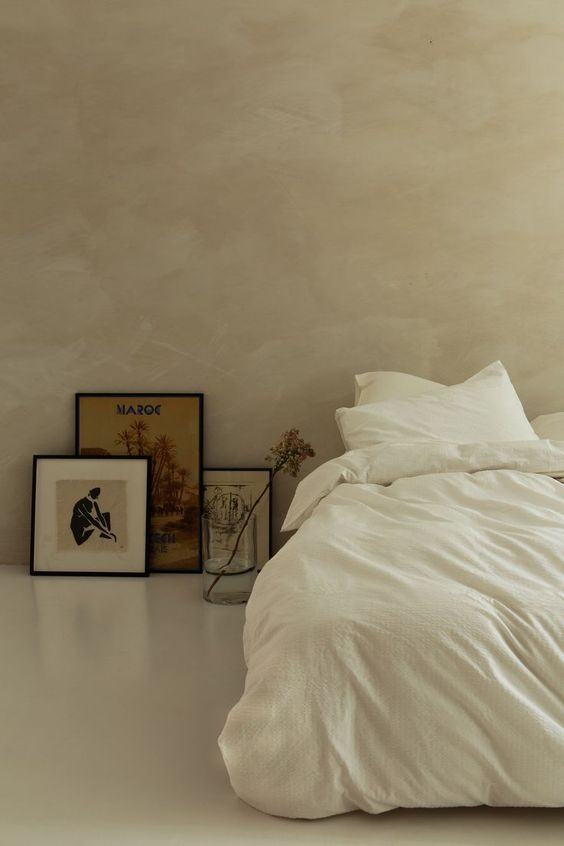 airy, warm, and minimalist bedroom idea white bed linen and duvet cover some framed works leaning on wall