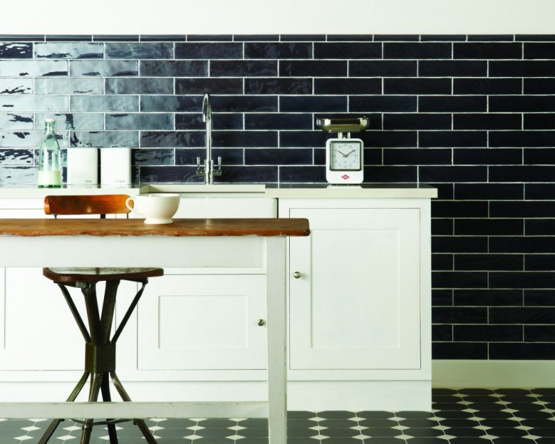 black metro tiled walls with white grout white kitchen counter and cabinets wood top dining table with stool