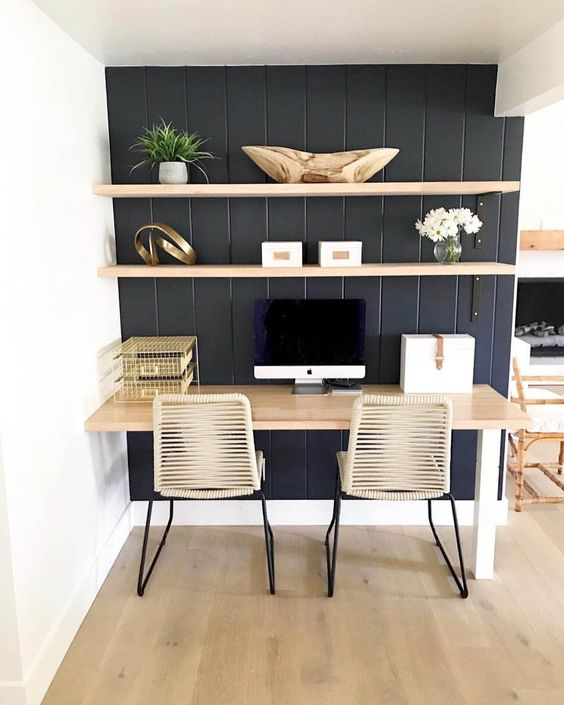 black painted wood plank wall wall mounted wood shelves light wood working desk wicker working chairs