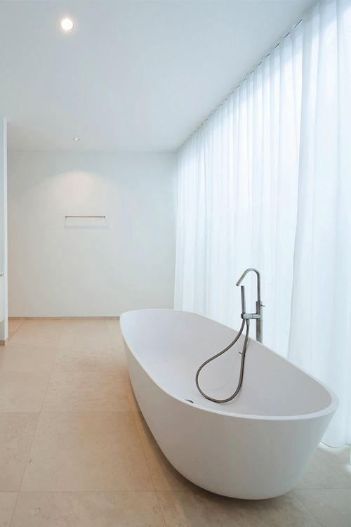 bright and airy bathroom design modern white bathtub soft neutral stone floors white walls and ceilings floor to ceiling curtains