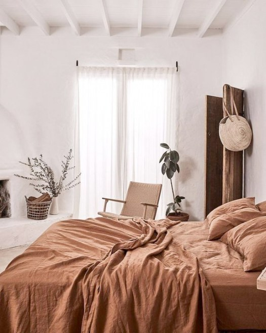bright and airy bedroom desig rust bed line wicker chair white walls white curtains potted houseplant white ceilings with white exposed wood beams