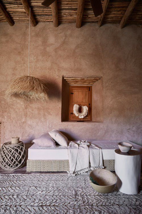 clay finish walls exposed wood beams and ceilings simple bed with white bed linen white throw blanket textural color area rug tree trunk side table