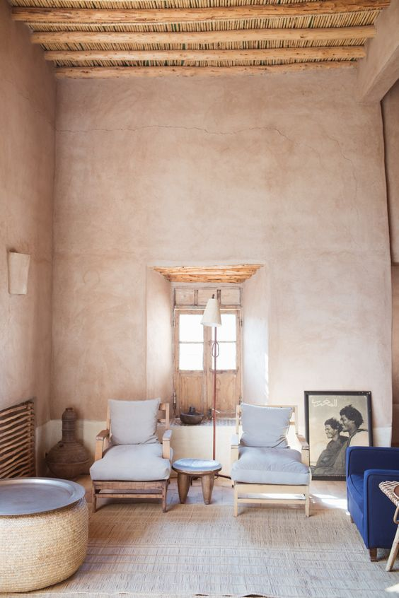 clay like walls exposed wood beams and ceilings a couple of lounge chairs with light blue cushions and wood frame deep blue sofa
