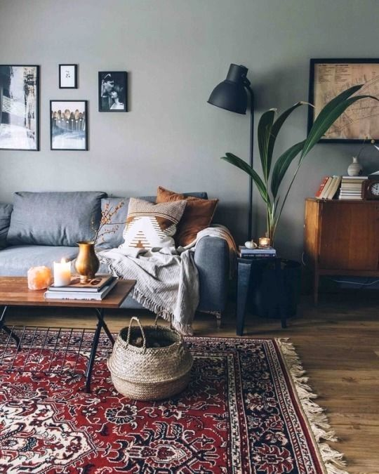 gray painted walls with framed photographs midcentury modern sofa in gray X base coffee table with wood top ornate basket vintage area rug black floor lamp