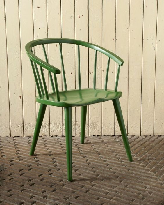 green vintage chair with angled legs and railed back