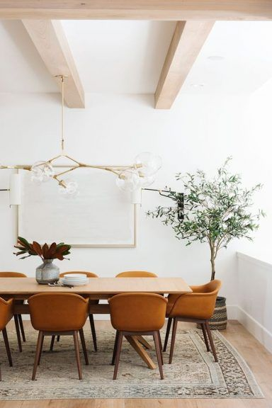light wood floors white walls and ceilings with light wood beams light wood dining table rust colored dining chairs with wood frame vintage area rug