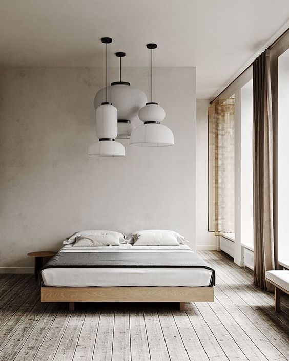 modern and minimalist bedroom oversized pendants with white lampshades minimalist wooden bed frame small bedside table wood plank floors white walls