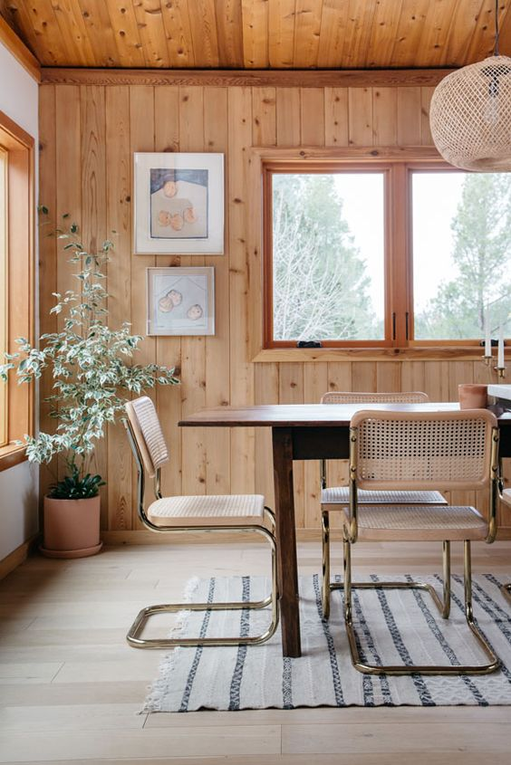 modern dining room in cabin in Malibu wicker dining chairs with stainless steel frame linen rug with simple motifs wood plank walls and floors