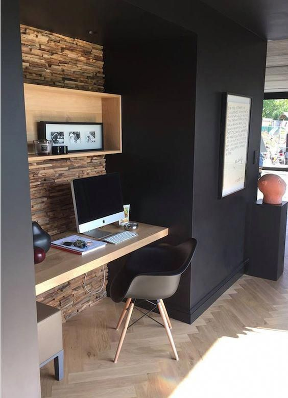 modern home office black walls accented with textural wood pallet at the center light wood working desk Scandinavian style working chair herringbone shaped wood floors