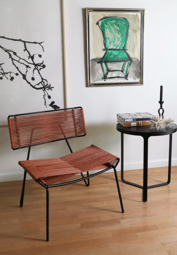 modern lounge chair with wire back and seater black metal side table wood floors