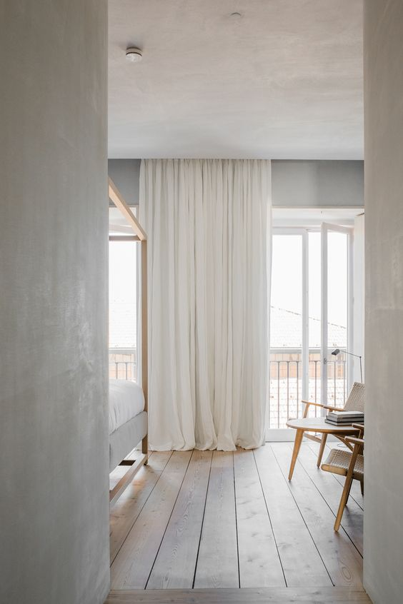 modern minimalist bedroom design floor to ceiling curtains in white light wood plank floors Scandinavian style bed frame with canopy a couple of Scandinavian chairs