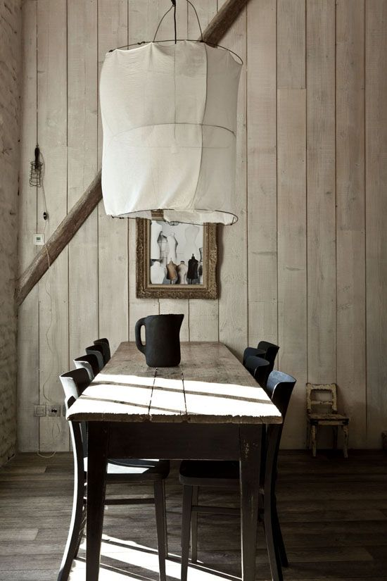 neo rustic dining space shabby wood plank walls shabby wood dining table black dining chairs oversized pendant with white fabric lampshade cover