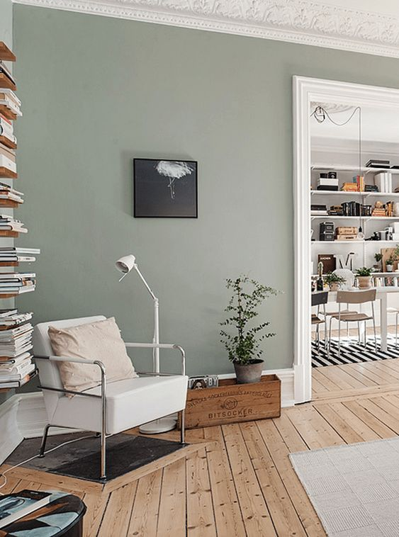 olive gray wall paint color wood plank floors vertical book shelf corner chair with stainless steel frame and white cushion modern white floor lamp