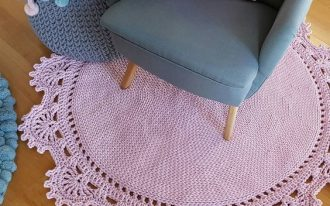 round shaped crochet rug in baby pink decorated with half way flower edges midcentury modern armchair in soft blue ornate crochet basket