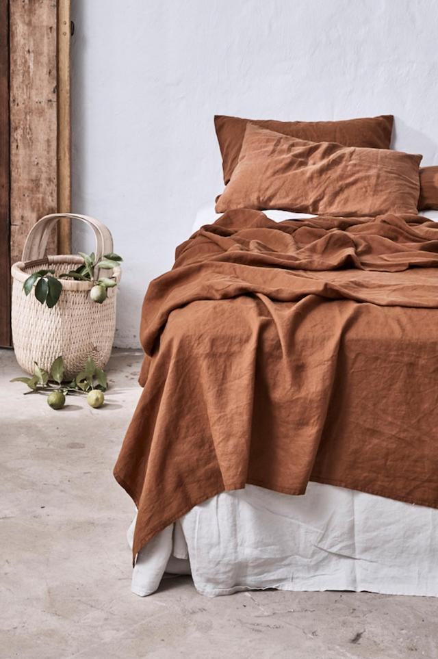 rust blanket and shams white bed linen wicker basket